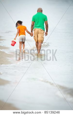 Father and daughter on the beach, walking hand in hand, father in thoughts, little girl beachcombing