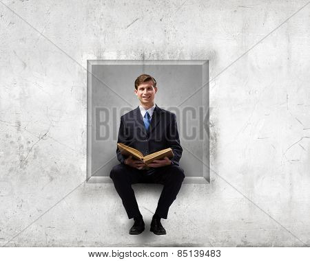 Handsome businessman sitting in white cube and reading book