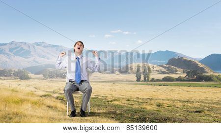 Young man outdoors sitting in chair and yawning