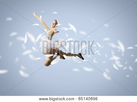 Young pretty ballerina girl making jump in dance