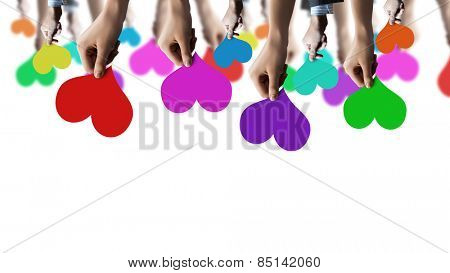 Close of many human hands with colorful cards
