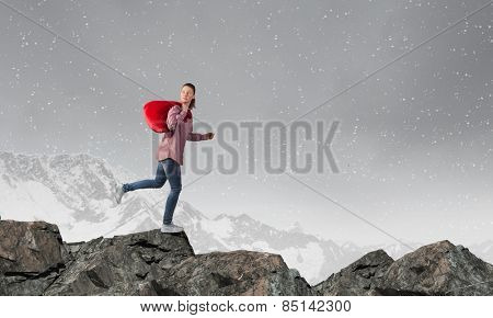 Young girl carrying red santa bag on back