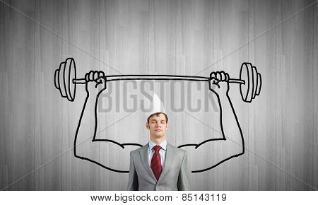 Young businessman in paper crown lifting barbell above head