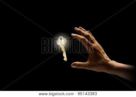 Close up of human hand catching golden key