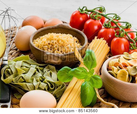 uncooked pasta and spices on a white wooden background