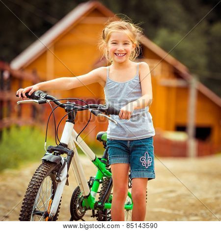 happy  girl with her bicycle in rural areas