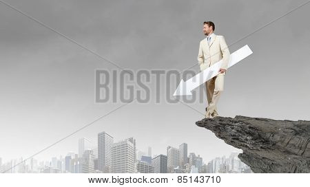 Businessman in suit holding white blank arrow in hands