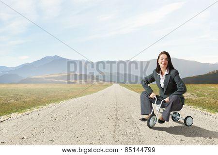 Young pretty businesswoman riding three wheeled bike