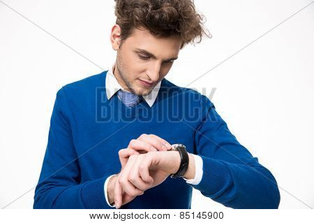 Confident businessman looking at watch over white background