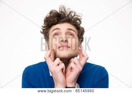 Young handsome man with crossed fingers over white background
