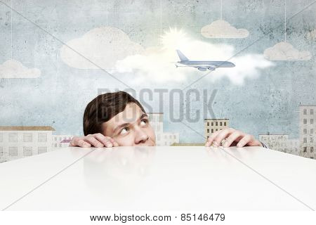 Young man looking from under table at flying airplane