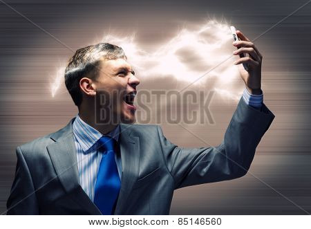 Angry businessman screaming furiously in mobile phone