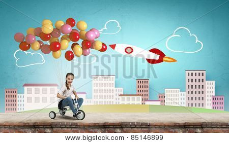 Cute girl against drawn background riding three wheeled bike