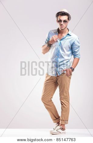 Full length picture of a young casual man posing on grey studio backgroud, holding one hand in his pocket while fixing his collar.