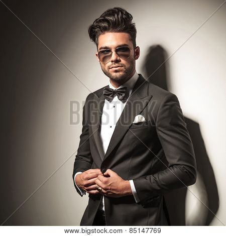 Handsome young elegant business man unbuttoning his jacket while looking away from the camera, side view picture,