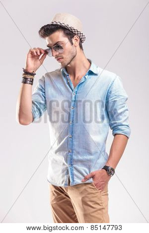 Young casual man holding one hand in his pocket while taking off his sunglasses, looking down.