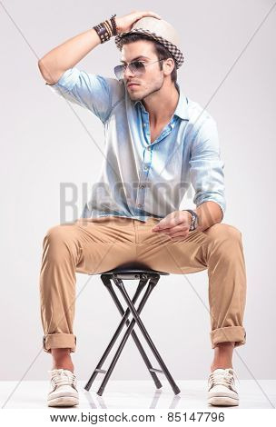 Attractive fashion man sitting on a stool on grey studio background, looking away while holding his hand on his hat.