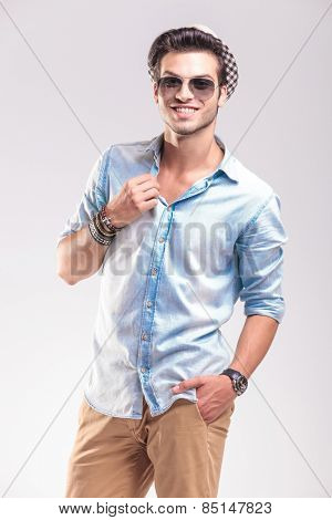 Happy casual fashion man smiling to the camera while fixing his collar with one hand in his pocket.