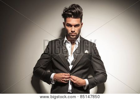 Handsome elegant business man looking at the camera while unbuttoning his jacket.