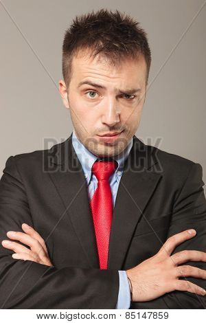 Young business man making a funny face over grey backgriund. He is holding his arms crossed while lifting one eyebrow.