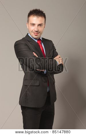 Side view picture of a handsome young business man smiling at the camera while holding his arms crossed.