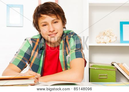 Cute handsome boy write in textbook and smile