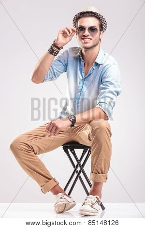 Smiling fashion man fixing his sunglasses while sitting on a stool, against studio background.