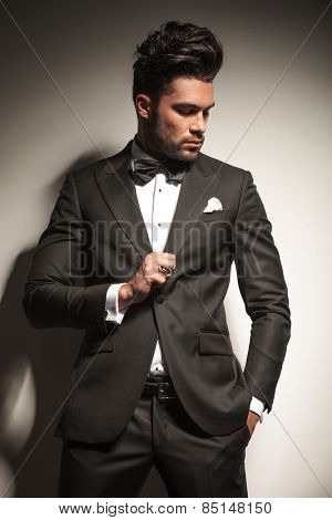 Portrait of a young business man holding one hand in his pocket while looking down.
