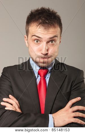 Funny business man holding his arms crossed, on grey studio background.