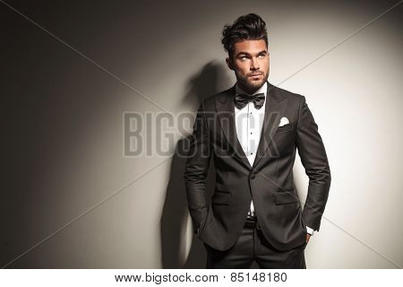 Picture of a young handsome business man looking up while holding both hands in his pocket.
