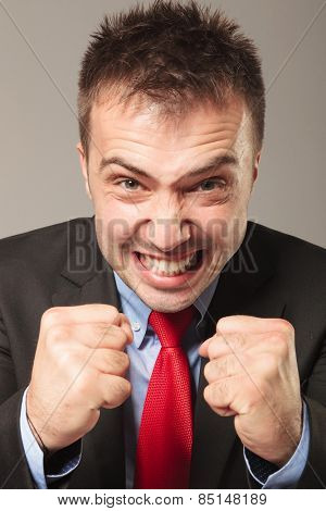 Furious business man making a angry face while showing you his fists,