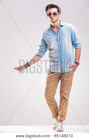 Young casual man posing on grey studio background while snapping his fingers, full body picture.
