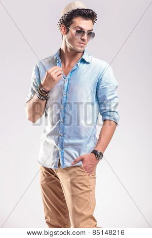 Picture of a young fashion man looking down while fixing his collar and holding one hand in his pocket.