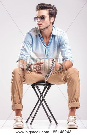 Young casual fashion man looking away while sitting on a stool, holding his hat in his hands.