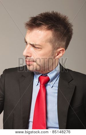 Side view picture of a young business man looking to his side while making a disapproving face.