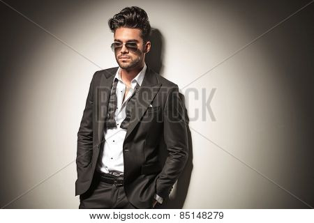 Attractive elegant business man leaning on a wall while looking down, holding both hands in his pocket.