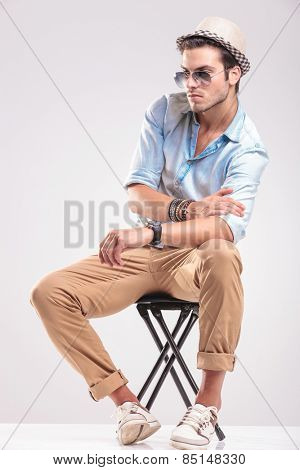 Fashion man looking down while sitting on a stool, fixing his sleeve.