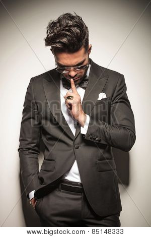 Elegant young business man holding one finger to his mouth whole looking down.