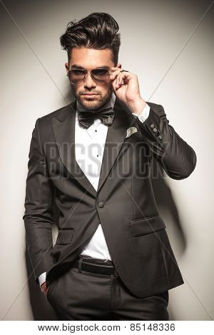 Attractive young business man taking off his sunglasses while holding one hand in his pocket.