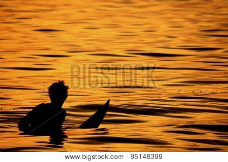 Surfer waiting for a set wave at sunset