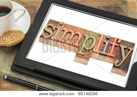 simplify word typography - text in letterpress wood type on a digital tablet with a cup of coffee