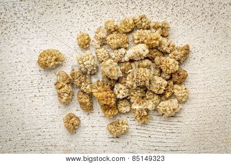 a pile of dried white mulberry fruit against rustic barn wood