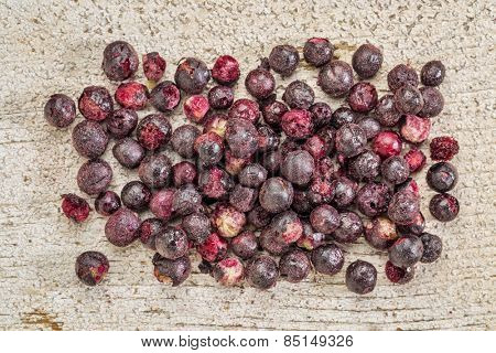 Freeze dried elderberries against rustic barn wood. Elderberries are rich in antioxidants and minerals which make them perfect in battling the common cold.