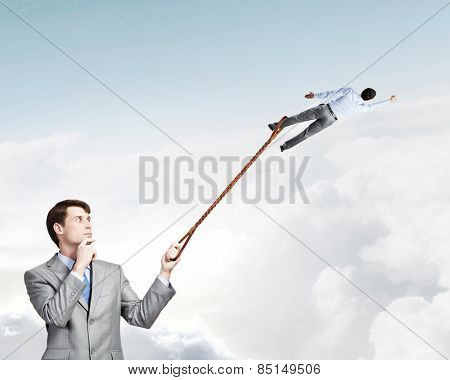 Businessman holding on lead another escaping businessman