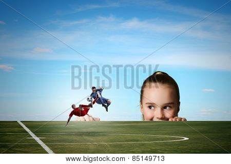 Little girl looking at two football players