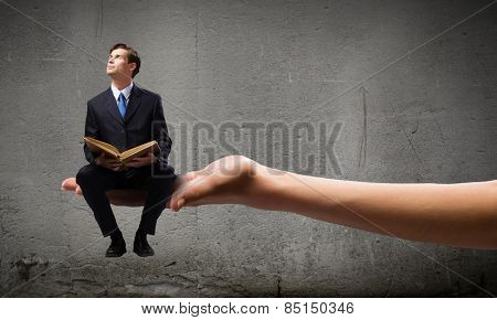 Handsome businessman sitting in cube and reading book