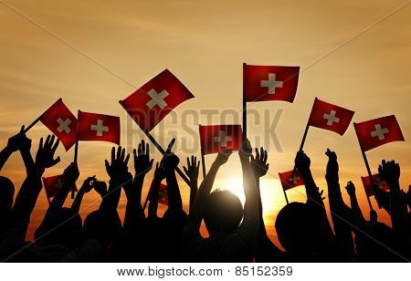 Group of People Waving Switzerland Flags in Back Lit Concept