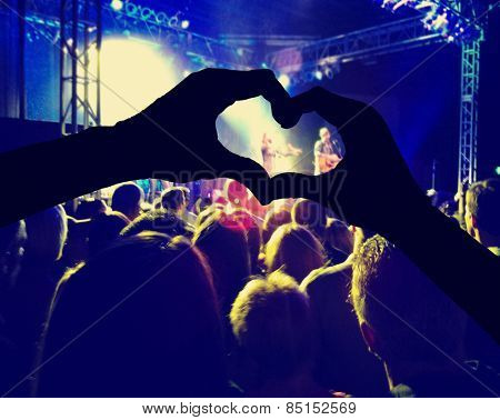 a crowd of people at a concert toned with a retro vintage instagram filter effect and hands making a heart shape in the foreground