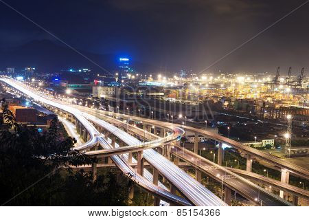 Illuminated and elevated expressway and cityscape at night