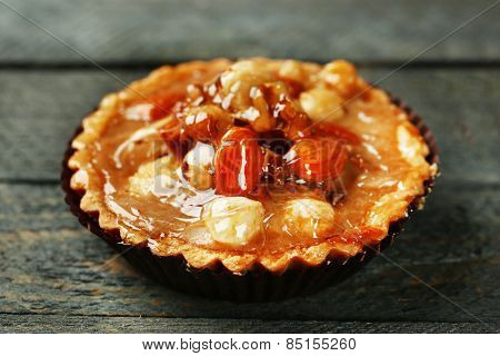 Mini cake with nuts on wooden background